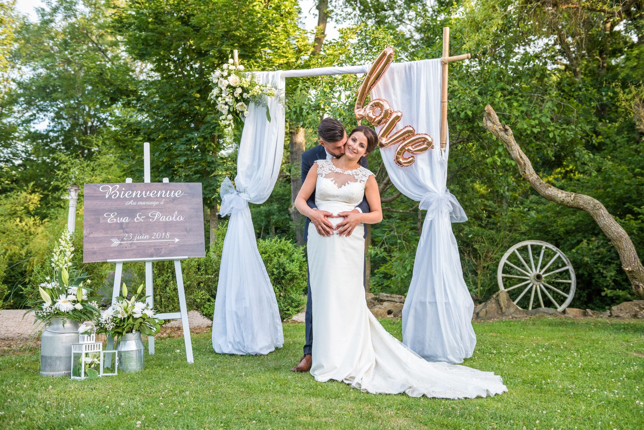 Couple de mariés sous leur arche de mariage dont l'organisation a été faite par Dj Art Song Production