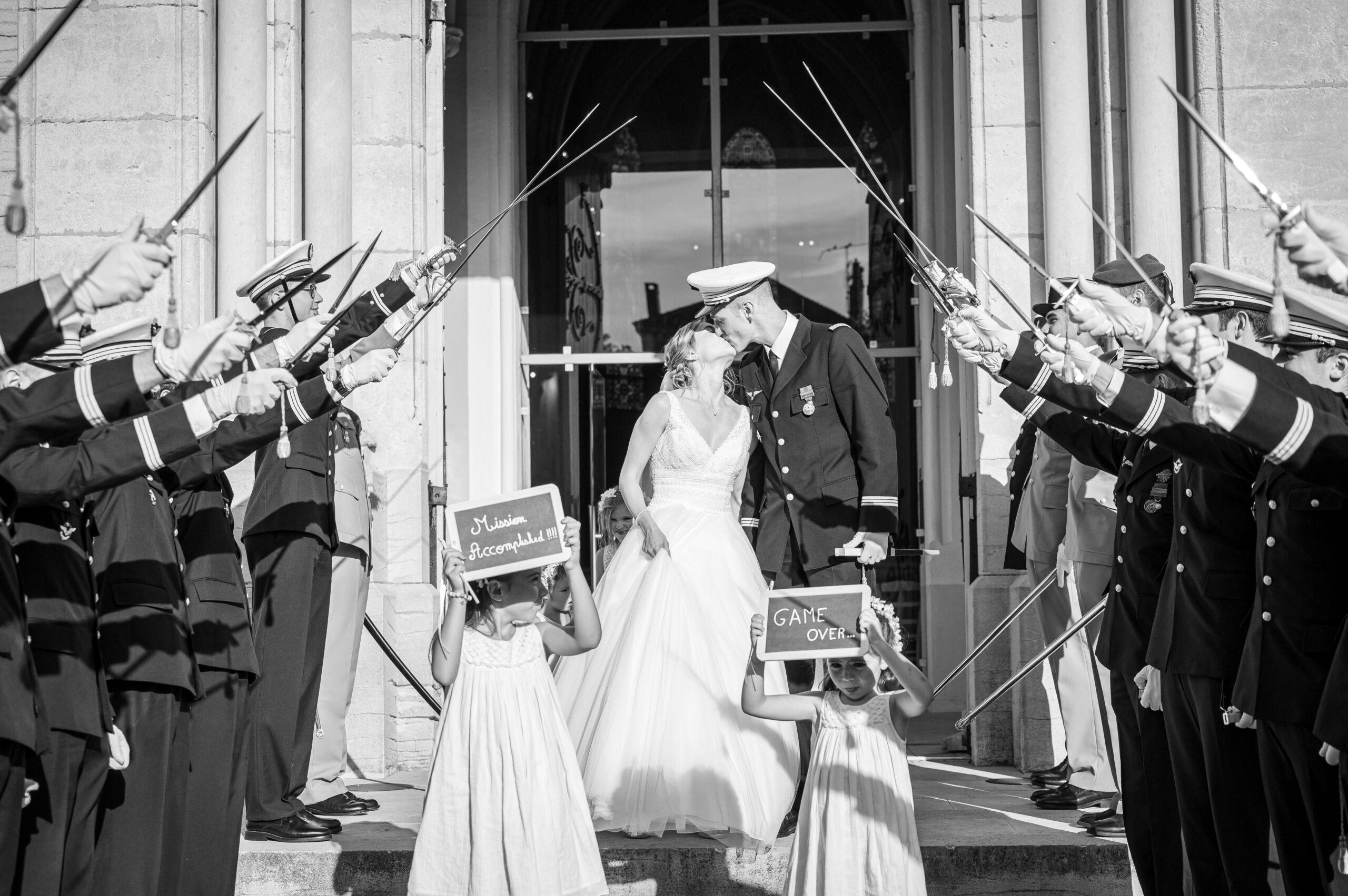 Photo en noir et blanc de la sortie des mariés de la cérémonie religieuse qui s'est déroulée au Perréon, dans le Beaujolais