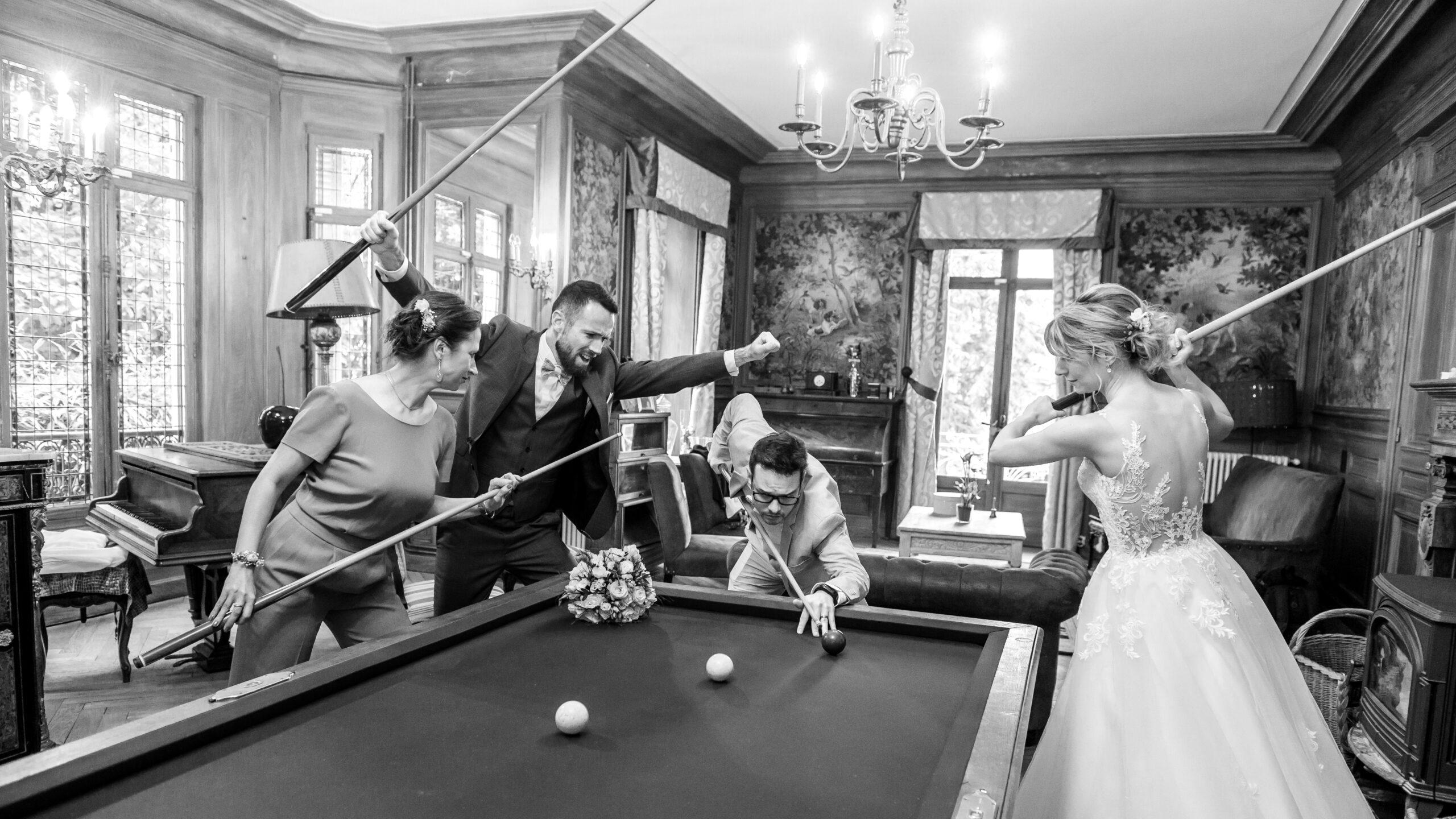 Photo en noir et blanc des mariés et leurs témoins en train de jouer au billard, dans le Beaujolais