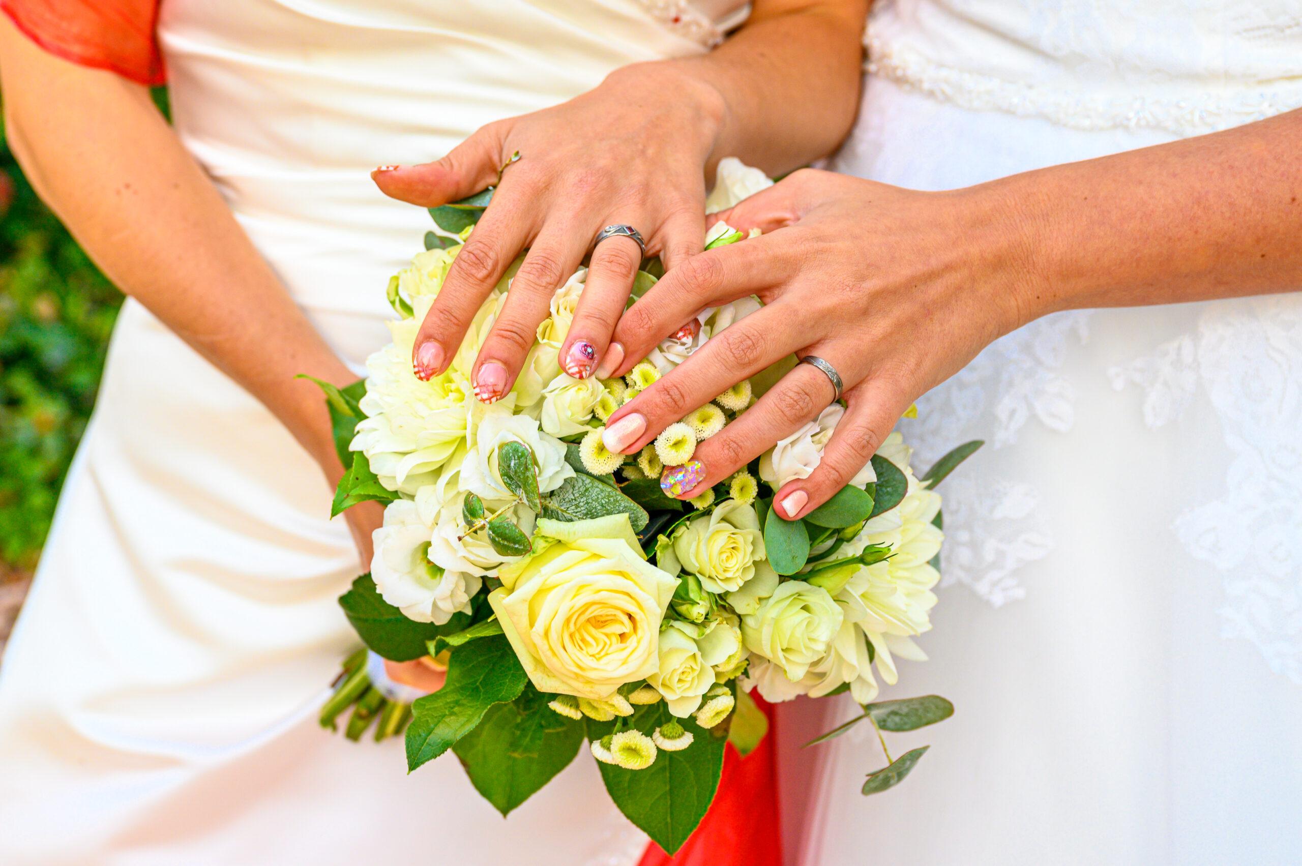 Photo du bouquet de mariées et des mains des mariées lors d'un mariage dans le Beaujolais avec la participation d'Art Song Production, professionnels de l'animation pour évènements privés et professionnels