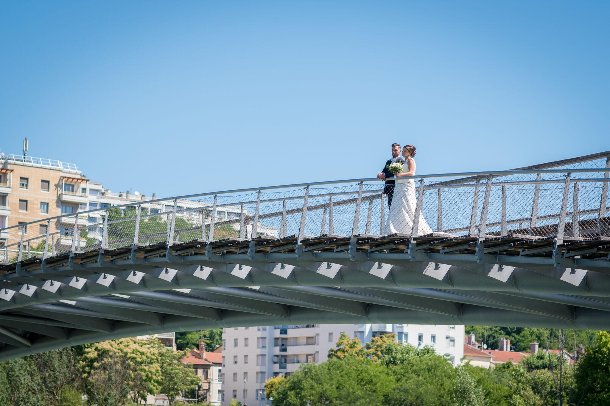 Photo en extérieur d'un couple de mariés sur un pont