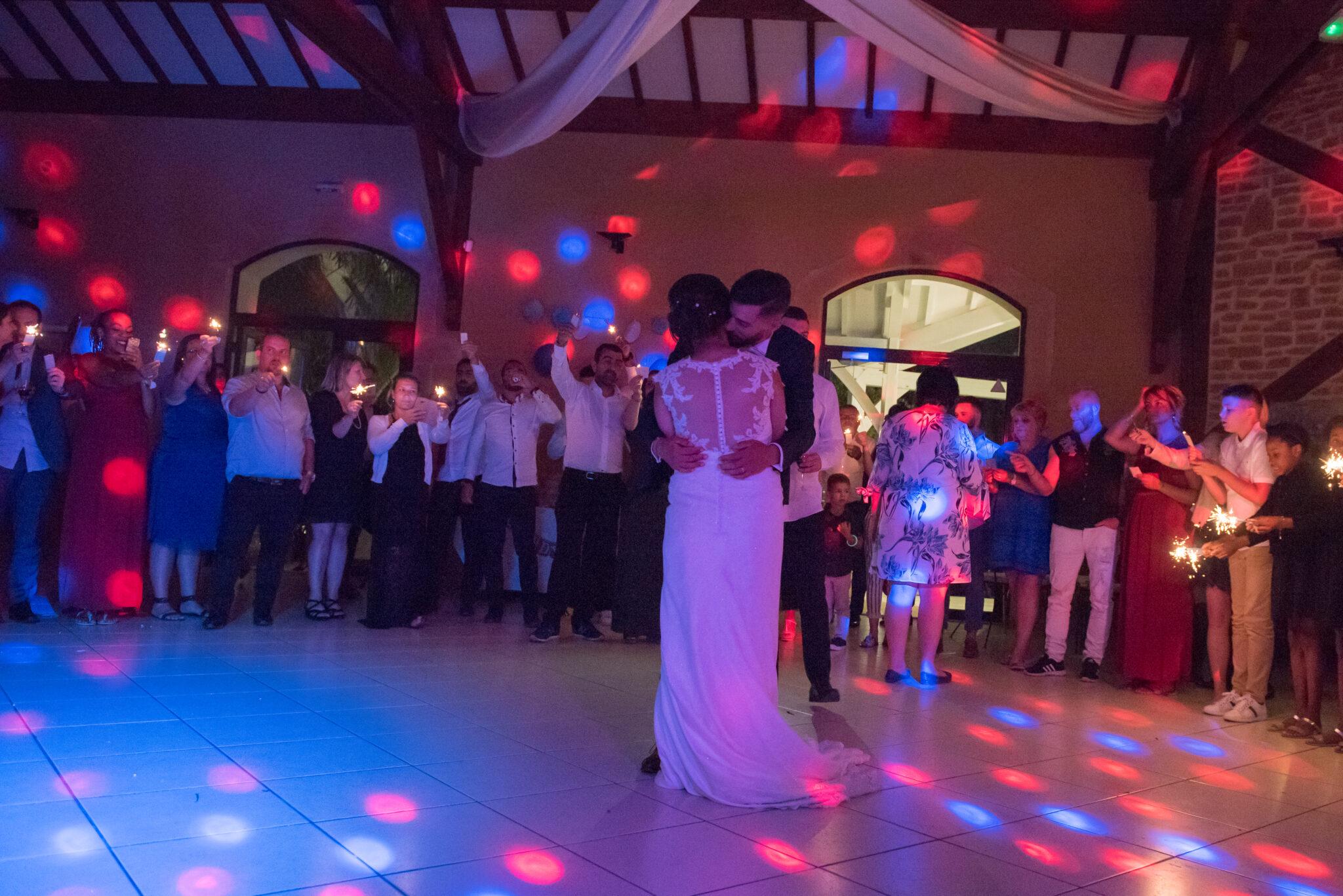 Couple de mariés en train de faire leur danse d'ouverture de bal avec les convives autour et les jeux de lumière installés et gérés par Dj Art Song Production