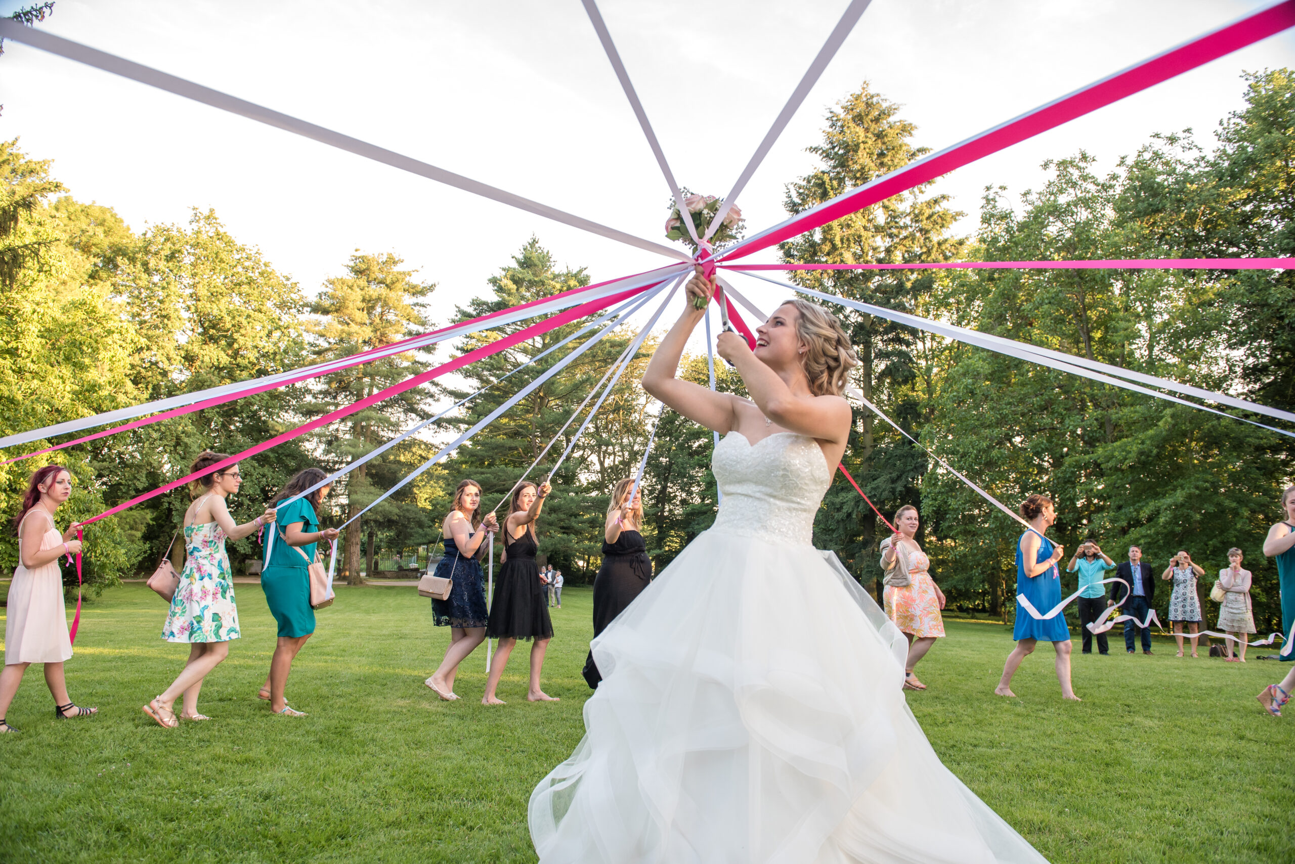 Mariée en train de tenir son bouquet en l'air et qui est relié aux convives par des bouts de tissus colorés, idée par Art Song Production