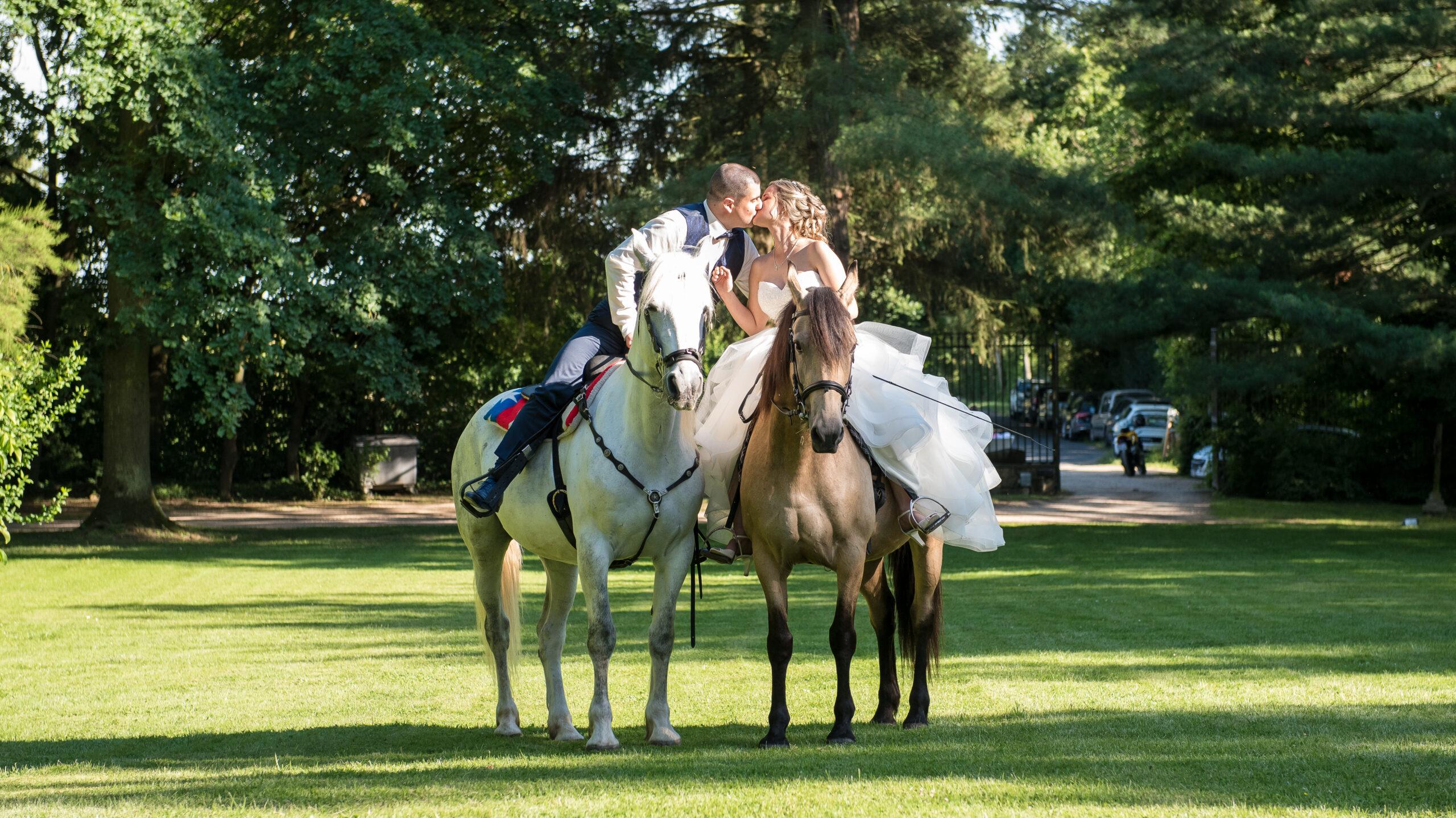 Mariés en train de s'embrasser, chacun sur leur cheval au milieu d'un très beau domaine dans le Beaujolais